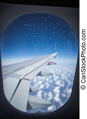 Clouds and sky as seen through window of an aircraft. Small ice crystals on the window