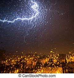 Clouds and thunder lightnings and storm over city. With drops on glass