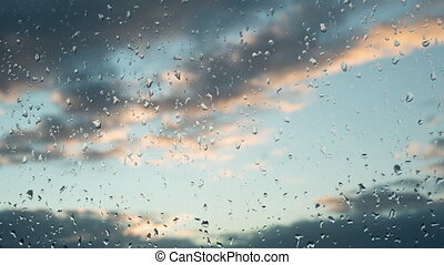 Clouds at sunset move across the sky. Raindrops on a window. After the rain. Good mood. Positive. All will be well
