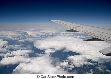 Clouds below - Commercial airliner at 30000 feet above the...