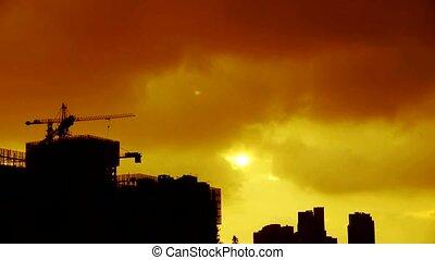 Clouds cover sun sky, building