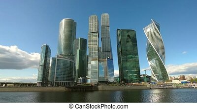Clouds drift toward the camera, casting shadows in timelapse over the modern skyscrapers of Moscow International Business Center in Russia. Video 4k DCI