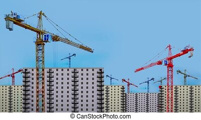 Contemporary different color tower cranes operate near multi-storey buildings at construction site against blue sky combined shot