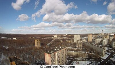 Clouds float low over city on blue sky, time lapse