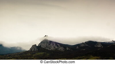 Clouds fly over a mountain peak - Clouds fly over a...