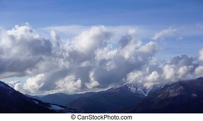 White clouds flying over Caucasus mountain landscape fade-out. Can be used for closing credits, titles. Time lapse.