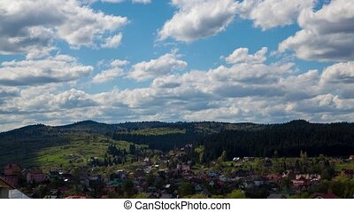 Clouds form in blue sky over small village. Time lapse -...