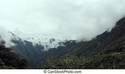 Clouds gathering at a mountainside - An establishing shot of...