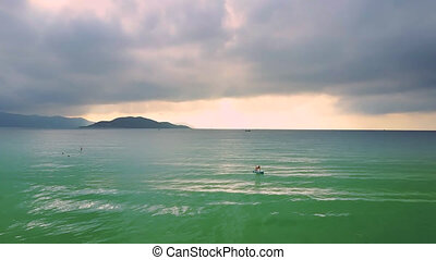 clouds hang above ocean and girl figure on paddleboard