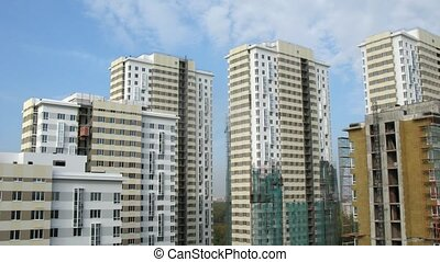 Clouds in blue sky float above considerable quantity of new buildings