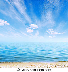 clouds in blue sky over sea and sand beach