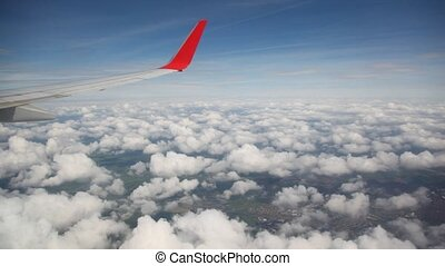 clouds in sky under wing of flying airplane