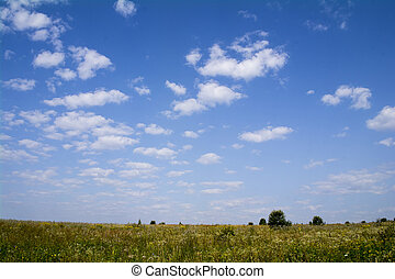 Clouds in the blue sky over farm fields