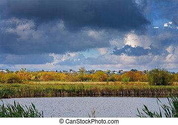 Clouds in the sky over the village, autumn meadow, forest and lake