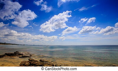 Clouds Motion above Stones in Transparent Shallow Sea Blue Sky