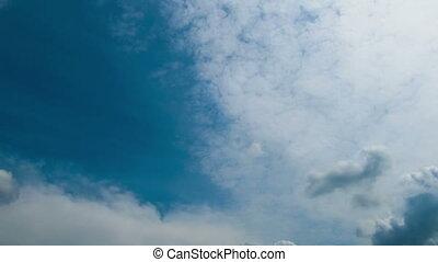 Clouds move across the blue sky.