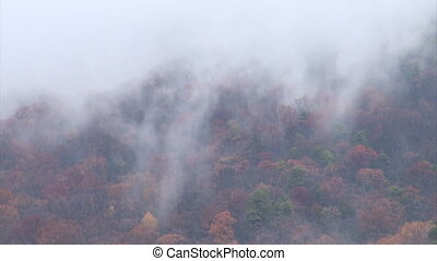 Clouds moving across mountains - Low clouds move over the...