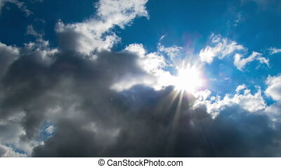 Clouds moving in the blue sky on the background of the bright sun.