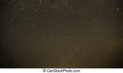 Clouds Moving in the Night Sky against a Background of Stars