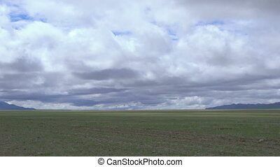 Clouds moving over green field