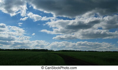 time lapse with clouds moving to you over green field with track