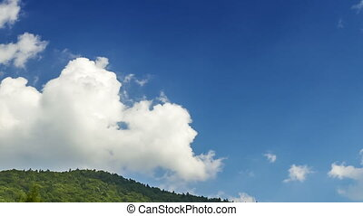 Clouds on blue sky over the hill