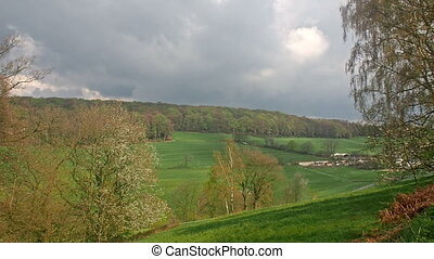 Clouds over a valley and a farm - A forest on the hill and...