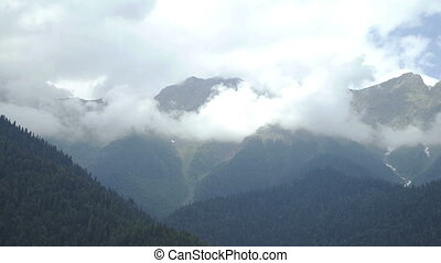 Clouds over mountain peaks with evergreen trees and blue sky...