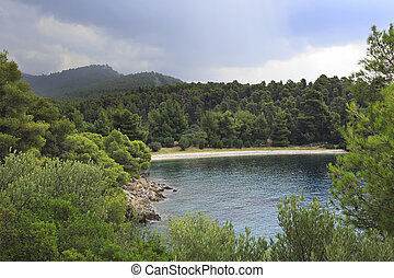 Clouds over mountains and sandy beach in the bay. Sithonia...