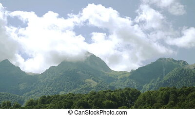 Clouds over mountains with evergreen trees and blue sky -...