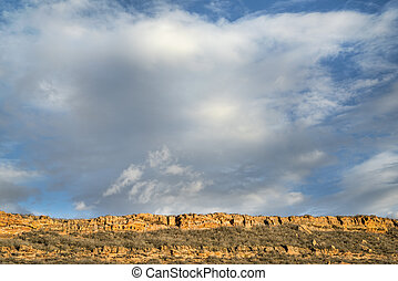 clouds over sandstone cliff