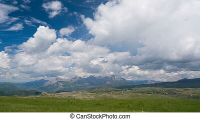 Clouds over the green meadow with majestic mountains in the...