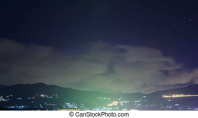 Clouds over the mountains at night. Time Lapse