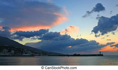 Clouds quickly move over the sea and a beacon at sunrise in Yalta, the Crimea