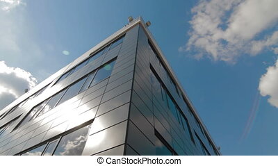 Clouds reflected in mirrored facets of modern office...