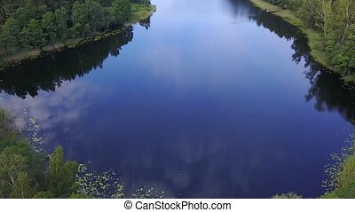 Clouds reflected in the mirrored water of the lake. Aerial survey