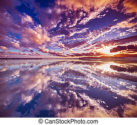 clouds reflected in the water at sunset
