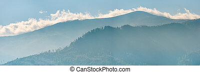 clouds rising behind the blue mountain - panoramic view of...