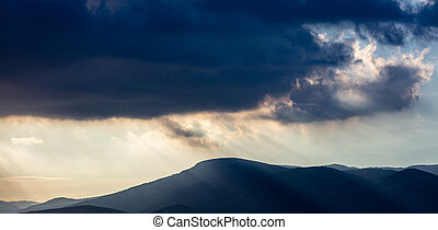 Heavy dark clouds on sky over mountains background.