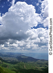 Cumulus clouds above hilly coast.