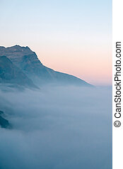 Cloudy alpine landscape with mountain range silhouette during sunset.