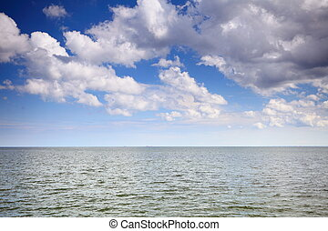 Cloudy blue sky above a surface of the sea