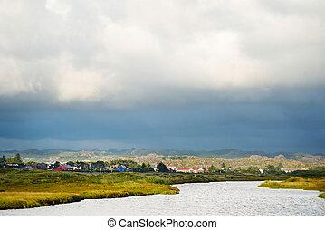 Cloudy landscape of norwagian village near the river