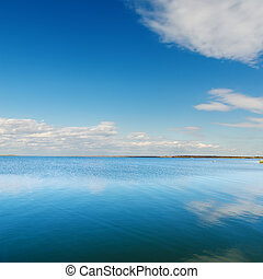 cloudy sky and deep blue river