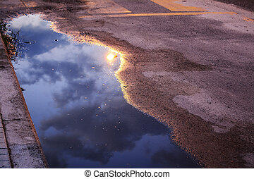 sky reflected in a puddle