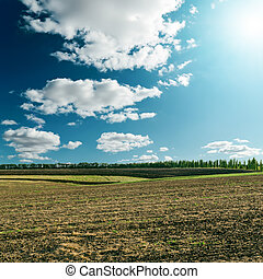 cloudy sky with sun over field