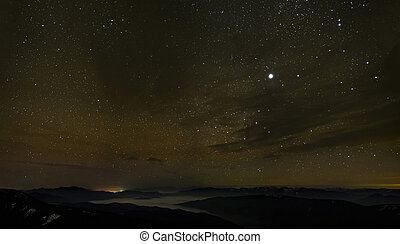 Cloudy starry sky over foggy mountains