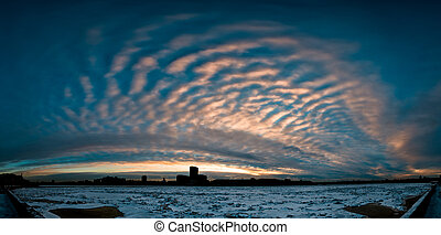 Cloudy sunrise in city