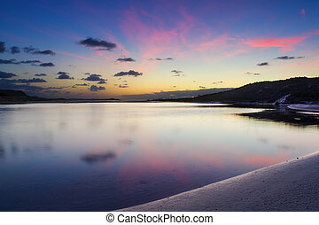 Cloudy sunrise over a quiet lagoon with cloud patterns reflected