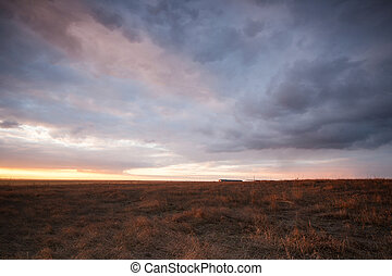 Cloudy sunset over fields